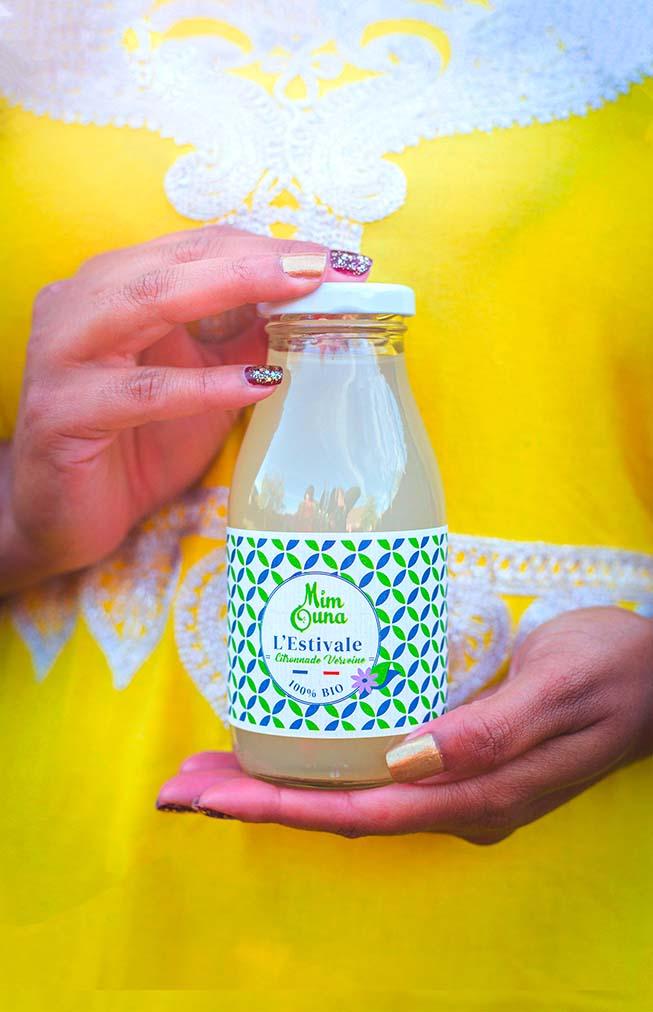 Main d'une femme en robe traditionnelle orientale tenant une bouteille d' authentique citronnade citronnade Mimouna à la verveine bio